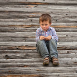 Offense of little boy. Boy is sitting on the logs and showing his offense Royalty Free Stock Photo