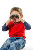 Boy sitting and looking through binoculars Stock Photography
