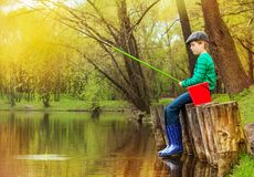 Boy sitting, looking at water and fishing on pond Royalty Free Stock Photos