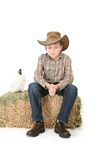 Boy sitting on lucerne bale Stock Photography