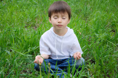 Boy sitting in meditation pose outdoor. Caucasian cute boy sitting in meditation pose outside on the grass Royalty Free Stock Photography