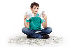 Boy sitting on money Royalty Free Stock Images