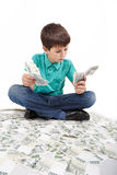 Boy sitting on money, money concept Royalty Free Stock Photography