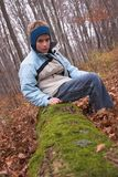 Boy sitting on mossy log. Boy dressed for cold weather in an autumn setting in a forest, sitting on a fallen tree/log covered with moss stock photo