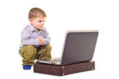 Boy sitting near a laptop Stock Photos