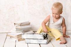 Boy sitting near retro typewriter and books Royalty Free Stock Photos