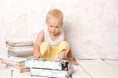 Boy sitting near retro typewriter and books Stock Image