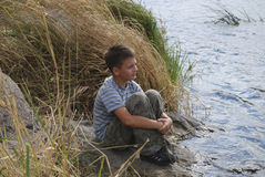 Boy sitting near the river Stock Photo