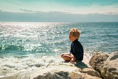 Boy sitting near the sea. Boy sitting on a stone and looking at the sea royalty free stock photos
