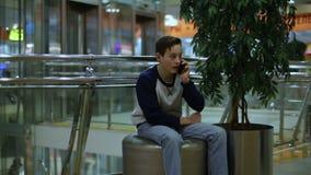 Boy sitting near tree and talking smartphone stock video