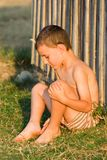 Boy sitting near wall Royalty Free Stock Photo