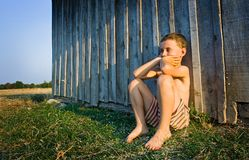 Boy sitting near wall. Little boy sitting on grass against a wall made of planks Stock Photography