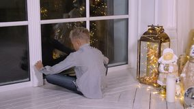Boy sitting near window at Christmas eve and waiting Santa Claus in living room. Boy sitting near window at Christmas eve and waiting red Claus in living room stock footage
