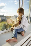 Boy sitting near the window. A boy in jeans and a white shirt. He is holding a teddy bear Stock Photography
