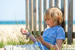 Boy sitting nex to wooden fence on beach. Royalty Free Stock Photos