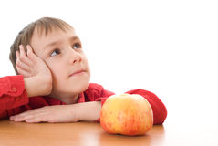 Boy sitting next to an apple and dreams Royalty Free Stock Photo