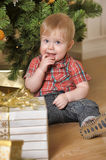 BOY sitting next to a Christmas tree and gifts. In his first CHRISTMAS Royalty Free Stock Photography