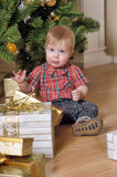 BOY sitting next to a Christmas tree and gifts. In his first CHRISTMAS Stock Images
