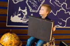 The boy sitting next to the globe. holding a big old book. Royalty Free Stock Image