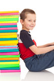 Boy sitting next to stack of books Stock Photography