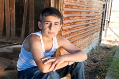 Boy sitting in old barn Royalty Free Stock Photos