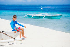 Boy sitting in old boat on the beach Stock Photography