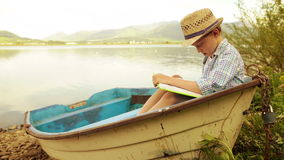 Boy sitting in an old moored boat reading a book stock footage