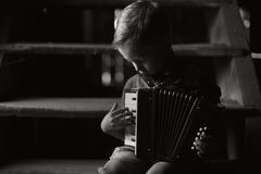 The boy is sitting on the old wooden stairs and playing the accordion. royalty free stock image