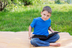 Boy sitting with opened album. On beach mat stock image