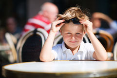Boy sitting in outdoor restaurant Royalty Free Stock Image