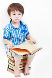 Boy sitting on pale of books Stock Images