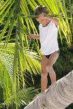 Boy sitting on palm tree Stock Image