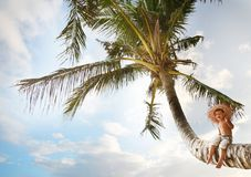 Boy sitting on palm tree over sky background Royalty Free Stock Images