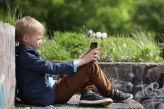 Boy sitting in park and using tablet pc. Educating and playing Stock Photo