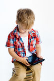 Boy sitting on a pile of books with tablet computer Royalty Free Stock Photography