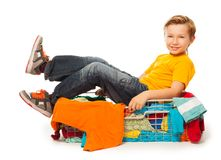 Boy sitting in pile of clothes Royalty Free Stock Image