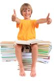 Boy sitting on piles of books. Young boy sitting on piles of books giving thumbs up isolated against a white background Royalty Free Stock Photo