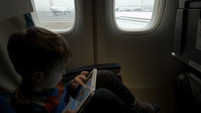 Boy sitting in the plane and using tablet PC stock video