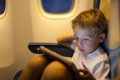 Boy sitting in the plane and using tablet PC Stock Image