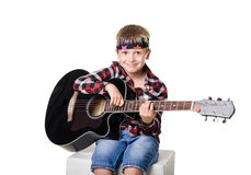 Boy sitting and playing with guitar Royalty Free Stock Image