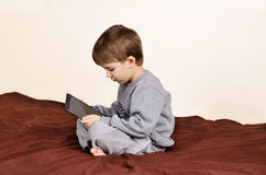 Boy sitting and playing on the tablet. Side view Stock Photos