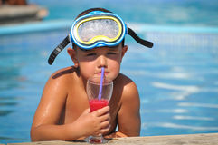 Boy sitting in the pool and drinking cocktails Royalty Free Stock Images
