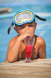 Boy sitting in the pool and drinking cocktails Stock Images