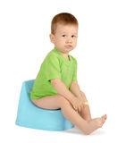 Boy sitting on a potty. Cute baby boy sitting on a blue potty isolated on white background Stock Photos