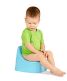 Boy sitting on a potty. Cute baby boy sitting on a blue potty isolated on white background Stock Photo