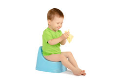 Boy sitting on a potty. Cute baby boy with eyes closed sitting on a blue potty isolated on white background Stock Photo