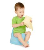 Boy sitting on a potty. Cute baby boy with toilet paper sitting on a blue potty isolated on white background Royalty Free Stock Image