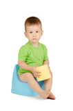 Boy sitting on a potty. Cute baby boy with toilet paper sitting on a blue potty isolated on white background Royalty Free Stock Photos