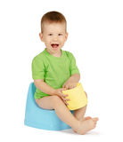 Boy sitting on a potty. Cute laughing baby boy with toilet paper sitting on a blue potty isolated on white background Royalty Free Stock Images