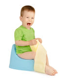 Boy sitting on a potty. Cute laughing baby boy with toilet paper sitting on a blue potty isolated on white background Stock Image